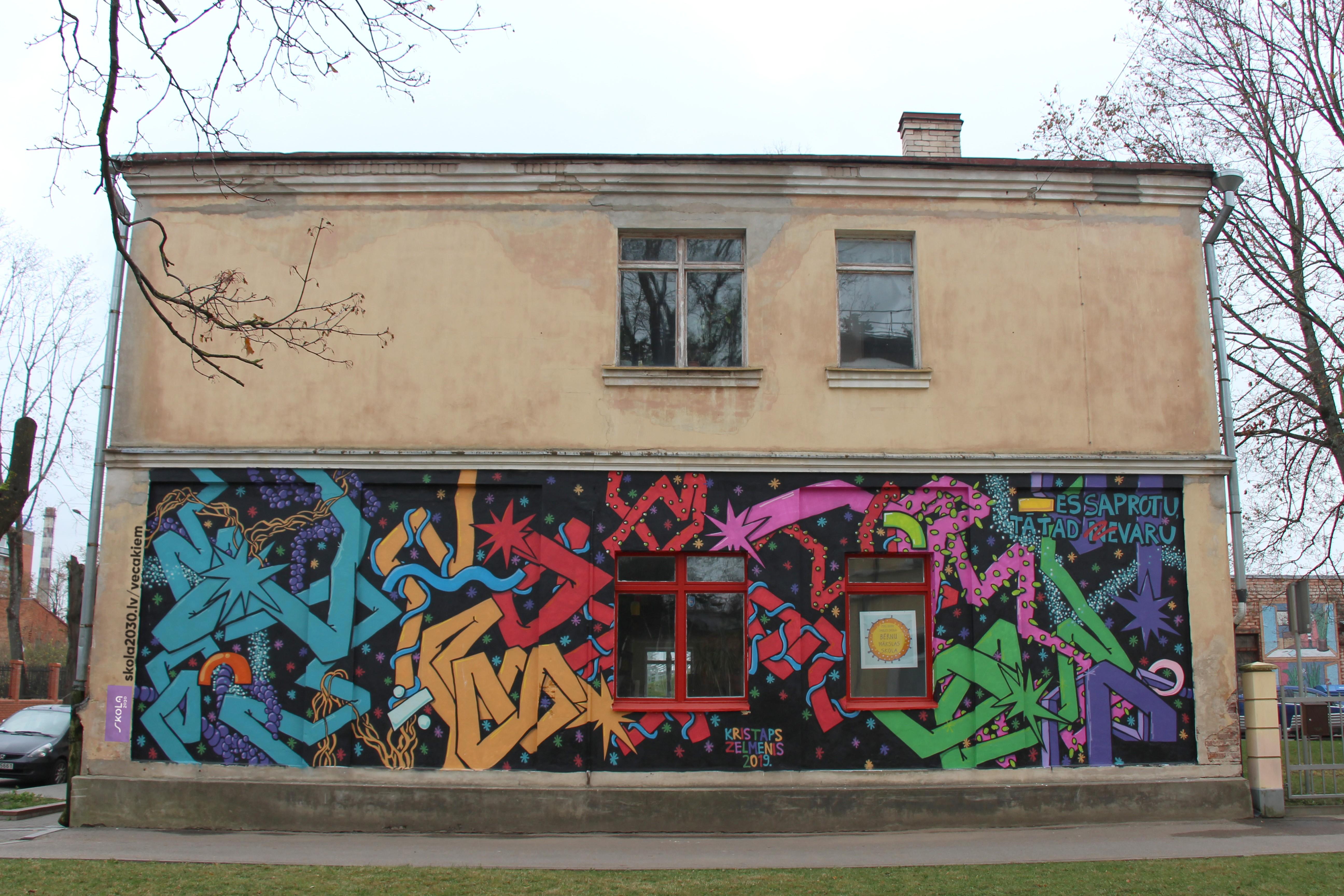 """Mākslinieks Kristaps Zelmenis kopā ar Daugavpils 3. vidusskolas un Daugavpils Dizaina un mākslas vidusskolas """"Saules skola"""" skolēniem ir radījis sienas zīmējumu, radošā veidā uzsverot – būtiska ir kvalitatīvas izglītības pieejamība katram skolēnam Latvijā."""